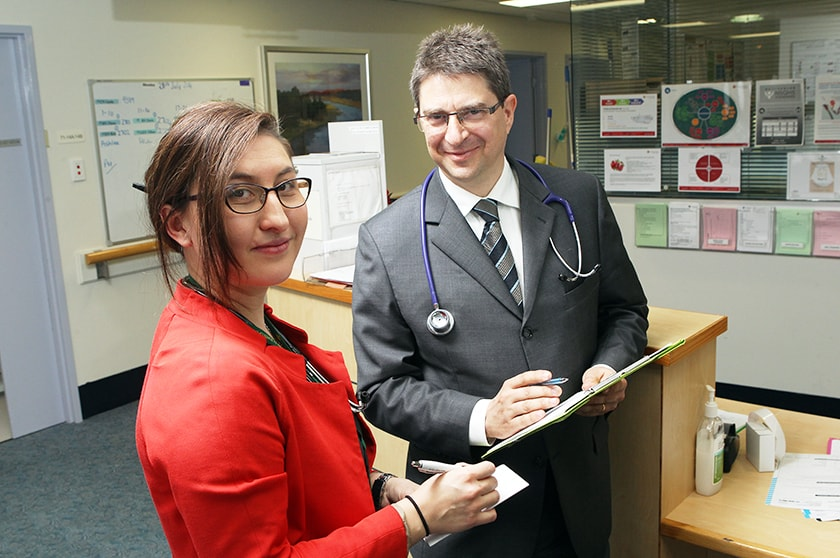 Two doctors consulting at nurses station.